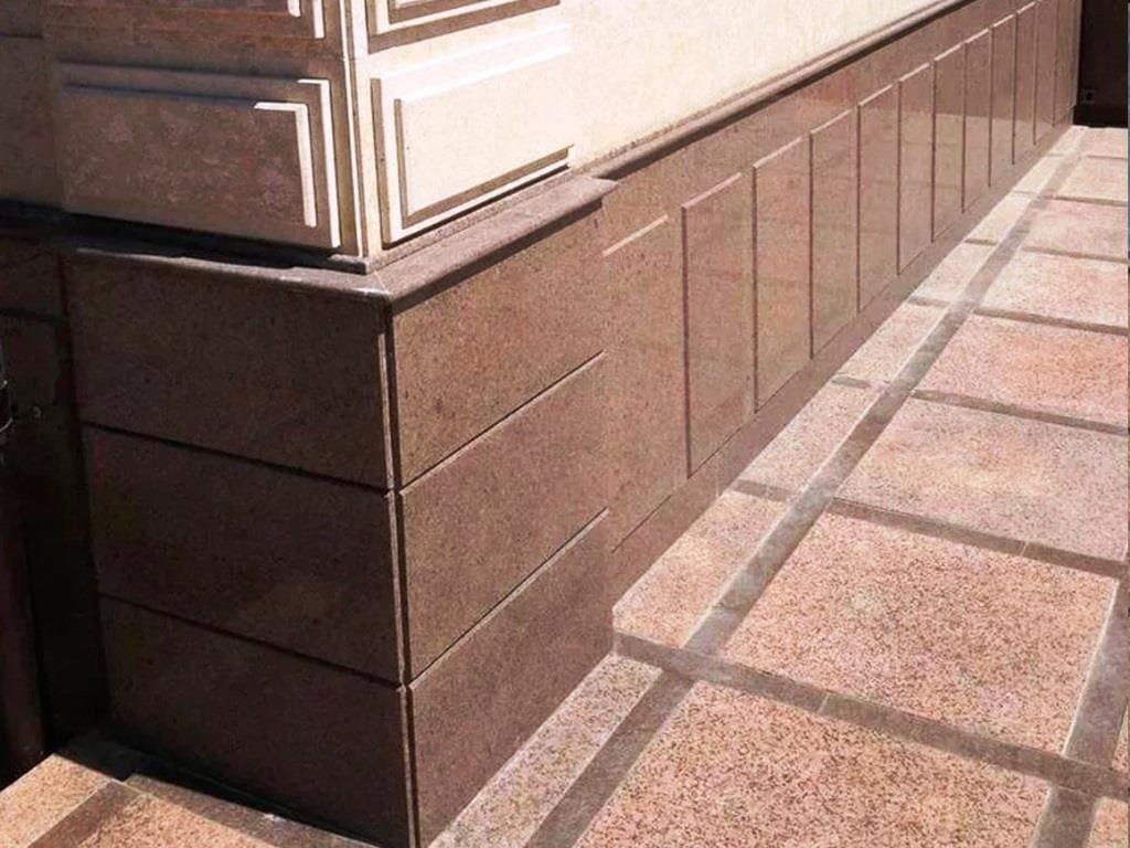 Цоколь здания облицован коричневым гранитом