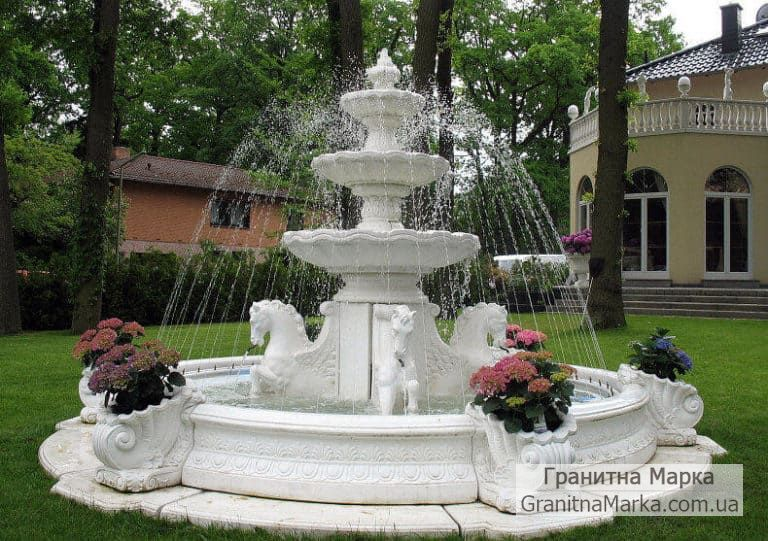 Белый мраморный фонтан со скульптурами лошадей